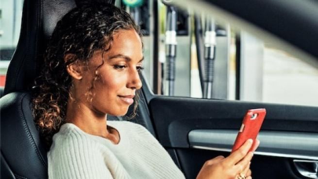 Woman in car, paying with her mobile phone