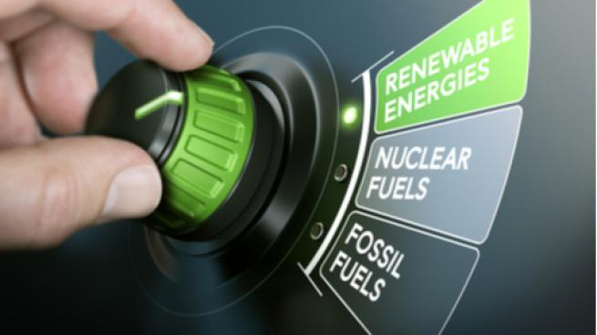 Man turning an energy transition button to switch from fossil fuels to renewable energies. Composite image between a hand photography and a 3D background.