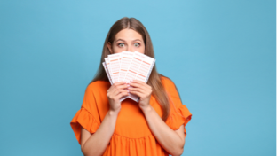 excited woman holding lottery tickets in front of her face
