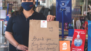 Little Short Stop Stores employee writes a personal note on the deliver item bag.