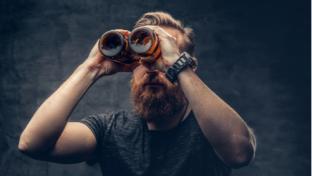 Funny redhead bearded male looking through two craft beer bottle like through binoculars.  F